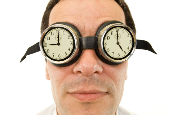 Man with clocks for glasses one showing 9am the other 5pm
