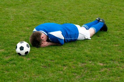 Footballer with head in hands lying on grass next to football - missed opportunity?