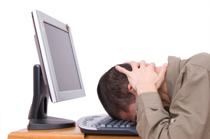 Man resting head on computer keyboard