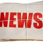 "The word ""news"" in red letters on white background on top of a pile of newspapers"