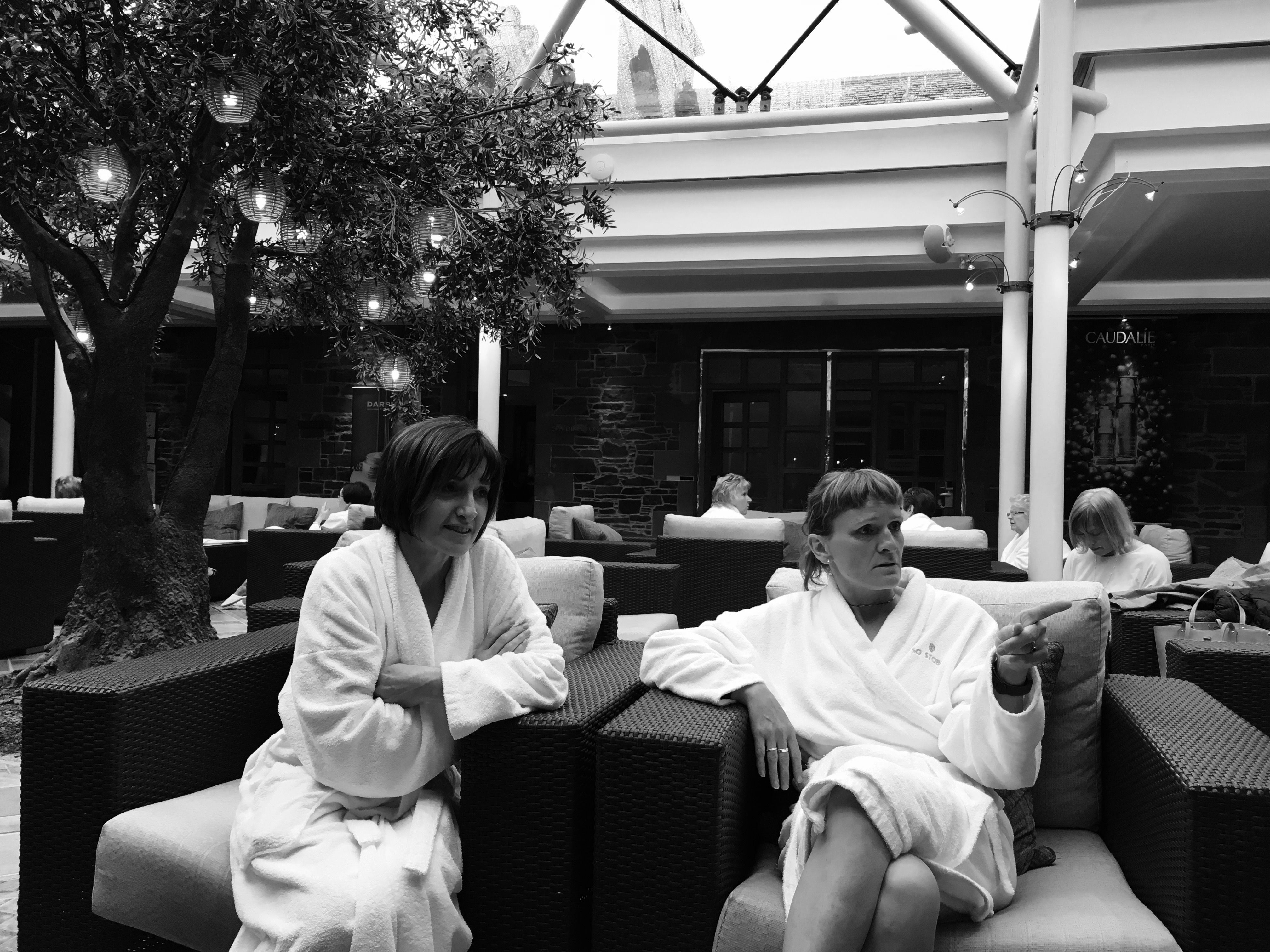 Ladies relaxing in white gowns in the lounge of a health spa