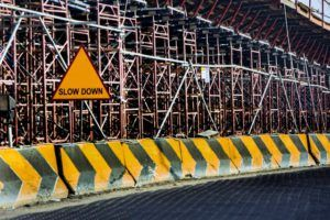 """Scaffolding with black and yellow hazard barrier at road level and sign saying """"slow down"""""""