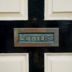 Close up of a black and white front door with a tarnished brass letterbox