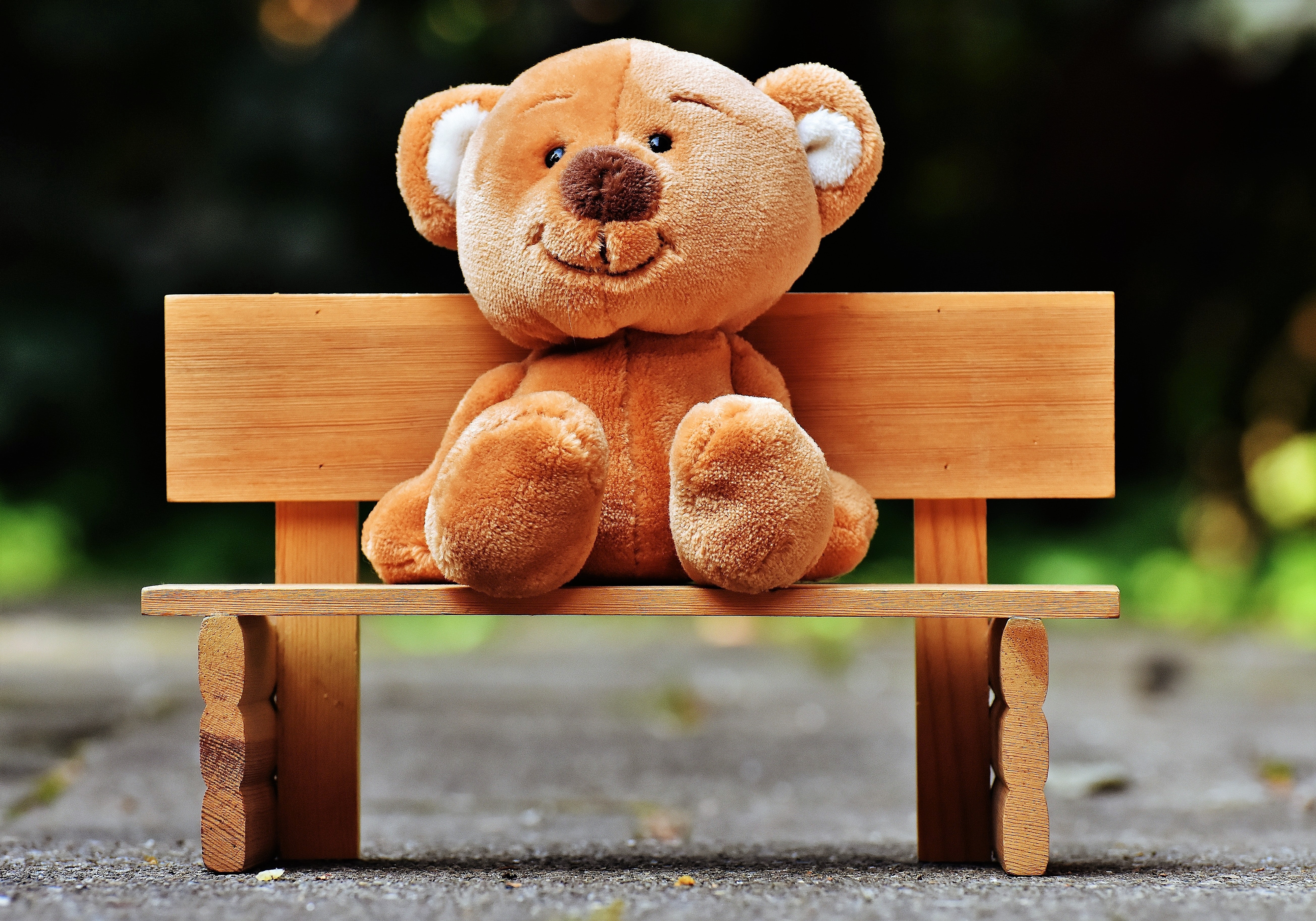 Smiling teddy bear sitting on a miniature wooden bench in a park