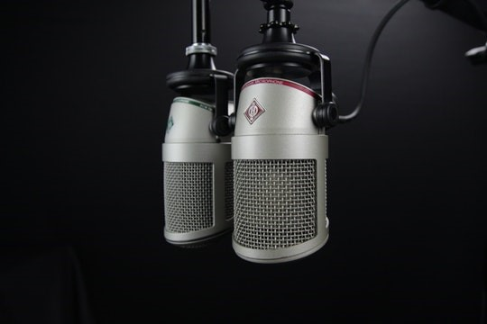 Black & white photo of two audio microphones hanging down
