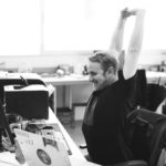 Black and white image of adult sitting at a desk and stretching