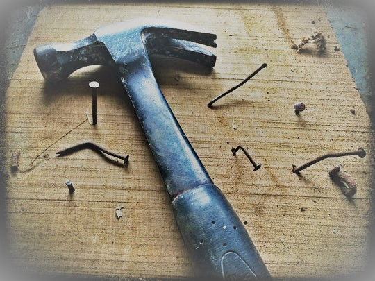 Black claw hammer on brown wooden plank with crooked nails