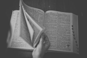 Black and white image of a hand leafing through a dictionary