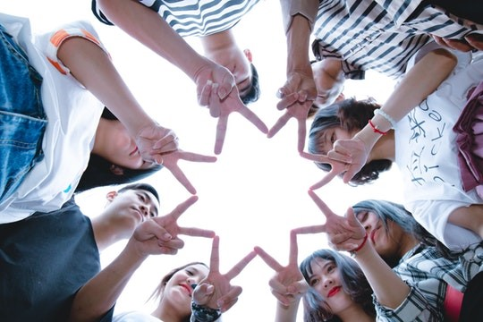 A circle of people forming a star shape with their fingers.
