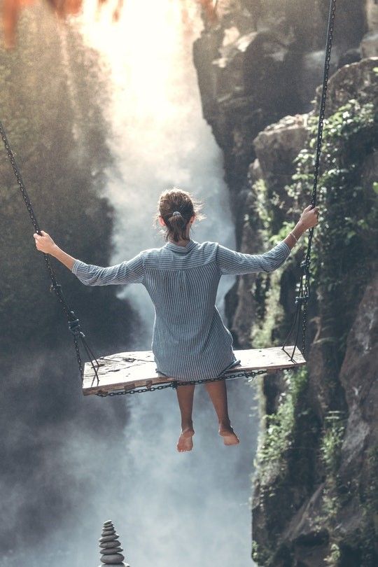 Woman sitting on a large swing overlooking a crevice with a misty waterfall ahead.