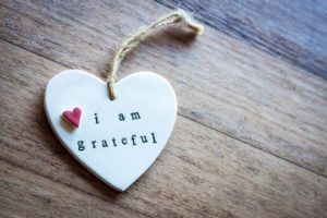 """A ceramic white heart on a wooden surface with the words """"I am grateful"""" and a pink heart inscribed on it."""