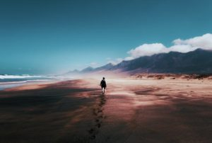 Person walking into the distance on a deserted beach