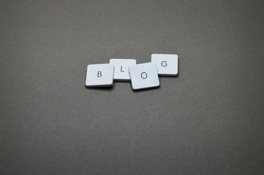 4 overlapping lightly coloured letter blocks spelling out the word Blog against a plain dark background