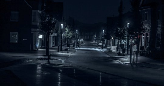 Black and white photo of a deserted town street in the dark lit by streetlights