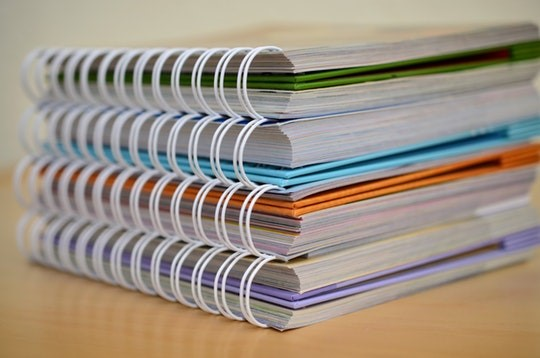 Stack of four brightly coloured spiral bound notebooks