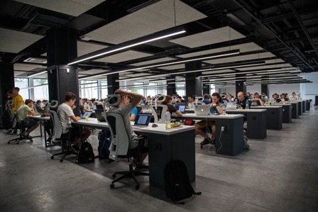 Open plan office full of people at desks working
