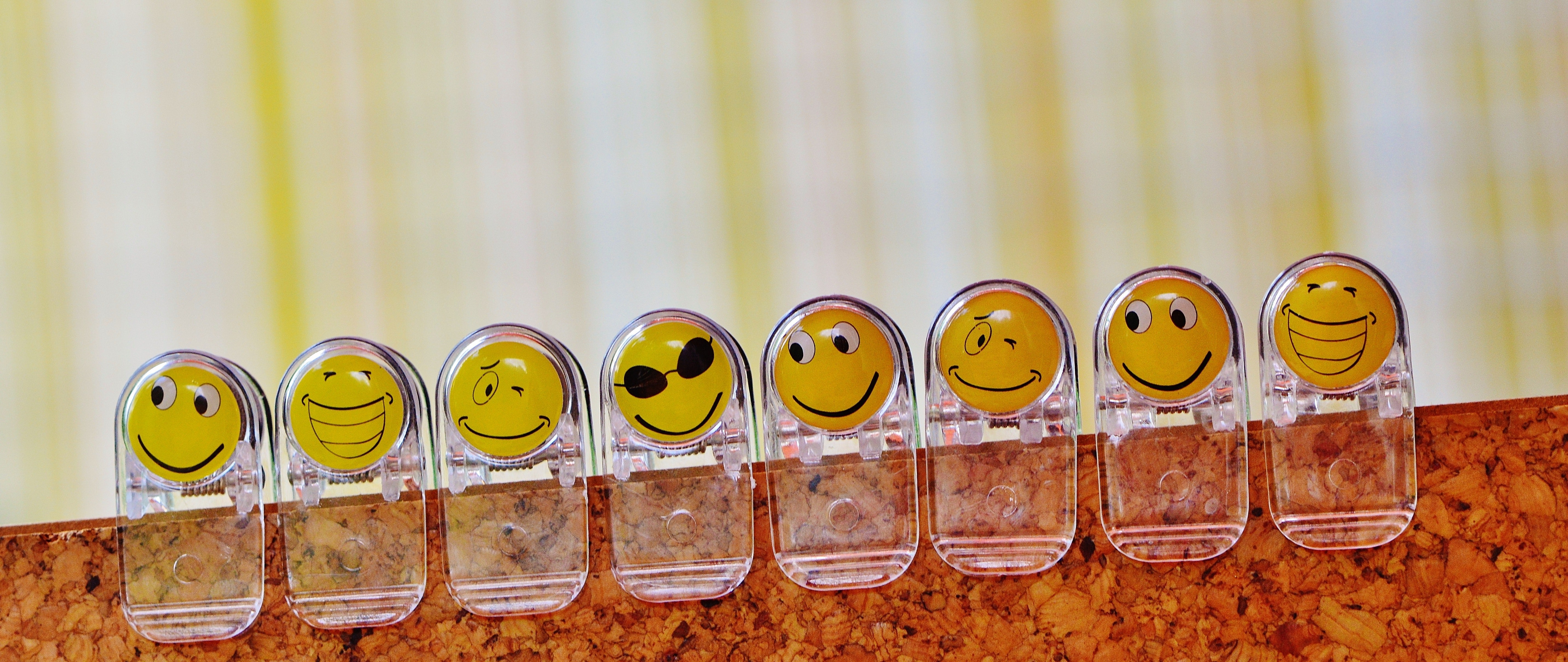 Clear clips with yellow heads showing various emoticon faces clipped in a row onto a cork board