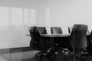 Black chairs around a wooden table in a meeting room.