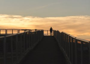 Silhouette of a person on walkway of a bridge