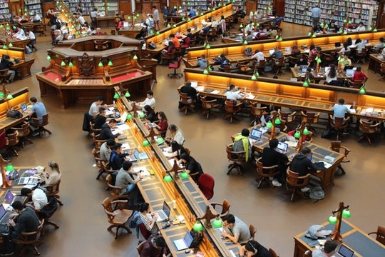 A large number of occupied study desks within an academic library