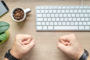 A desk with a keyboard, cup full of coffee beans and a person's clenched fists resting on the desk