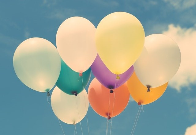 An assortment of nine coloured balloons on strings against a very slightly cloudy blue sky