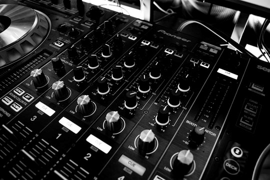 Close up photo of a black and silver music mixing board