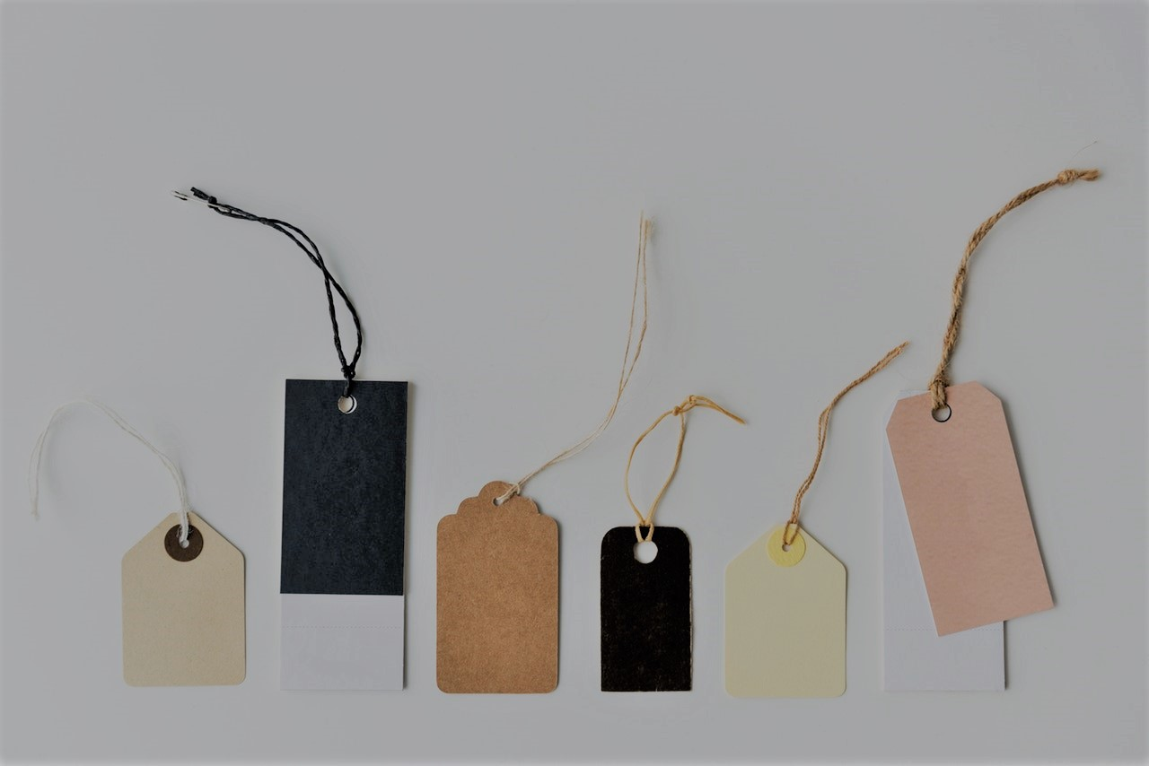 A row of assorted coloured, sized and shaped tags with strings.