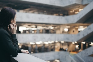 Staff member looking over balcony in office