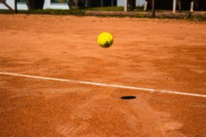A tennis ball bouncing just inside the line on a clay tennis court