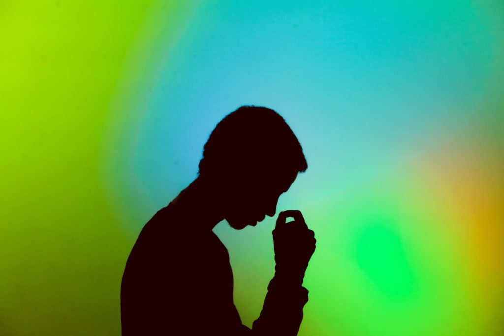 Silhouette of a young man with a swirl of bright green, blue and yellow colours in the background