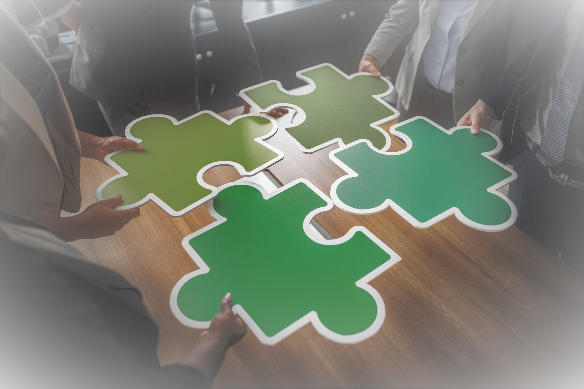 4 people standing around a table each holding a huge jigsaw piece