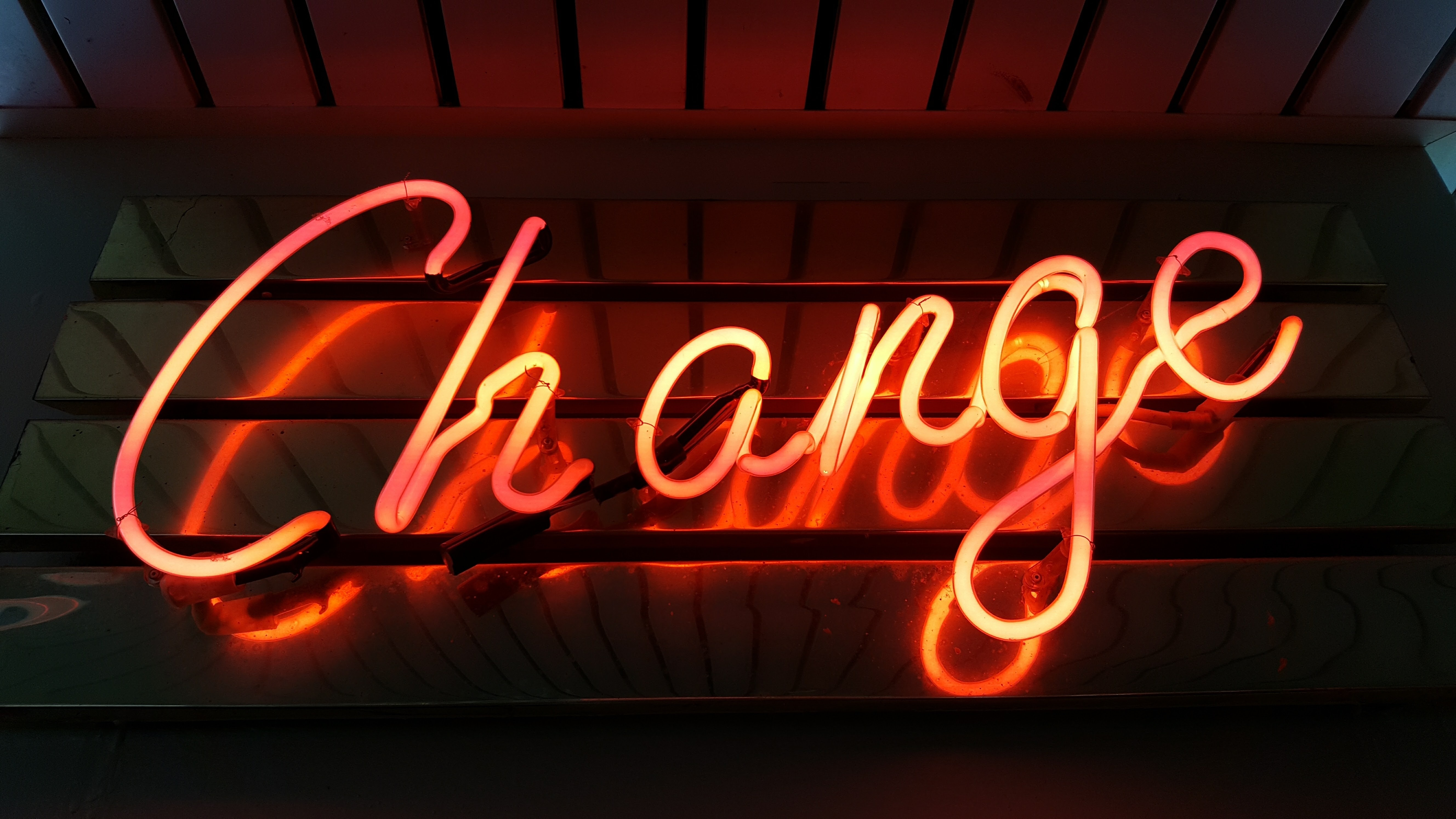 Illuminated fluorescent tube spelling the word Change on a slatted metal base.