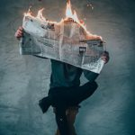 Man sitting cross legged on a stool reading a broadsheet newspaper the top of which is on fire