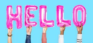 5 people's hands holding up pink lettered helium balloons spelling out the word Hello