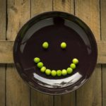 A brown ceramic plate with a smiley face made out of green peas.