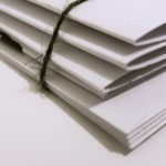 Close up photo of some white paper folders bound together with dark twine