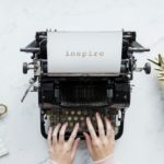 Old fashioned typewriter with a piece of paper in the rollers and the word 'inspire' typed in large letters