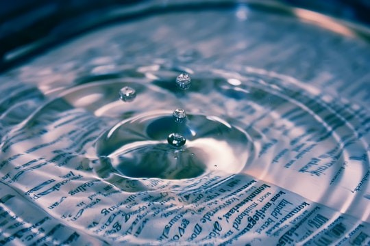 A printed page underneath some shallow water and a water droplet forming rings on the surface