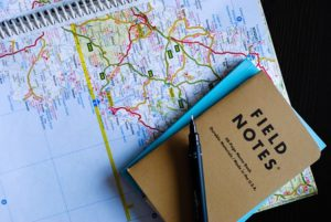 An open spiral bound road map with a field notebook and pen on top.