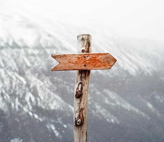 A blank wooden arrow sign on a bare wood post with a hilly backdrop