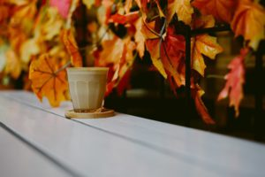 Brown ceramic mug on a wooden table with the backdrop of a trailing branch with colourful Autumn leaves
