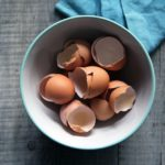 Brown egg shells in a white bowl on a wooden surface, photo taken from above.