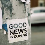 "A lamppost with peeling paint that has a black and white notice pasted to it reading ""Good news is coming""."