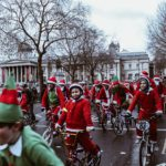 Lots of children and adults on bikes, in Santa and Elves outfits in Trafalgar Square, London.