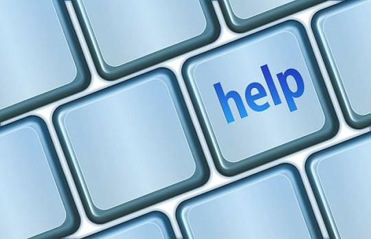 Photo of some blank blue-grey keyboard keys with 'help' written in blue on one key