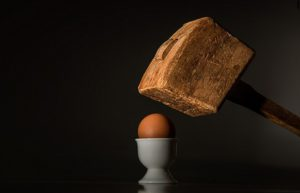 A wooden mallet held over a boiled egg sitting in an white china egg cup