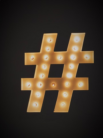 A black background with a hashtag sign in gold, illuminated with little bulbs