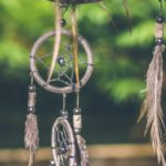 A grey and black dream catcher with a soft focussed tree in the background