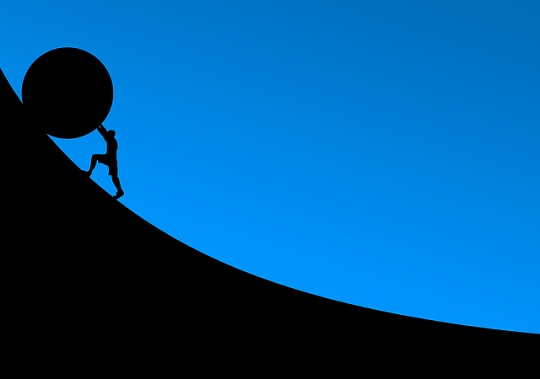 Silhouette of a figure rolling a large stone up a hill